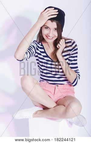 Youth Lifestyle Concepts and Ideas. Portrait of Happy Smiing Caucasian Brunette in Hat and Striped Shirt Posing in Studio Against White. Vertical Image Composition