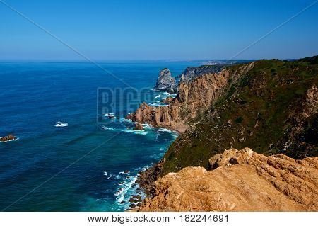 Impressive Landscape with Stormy Ocean and High Sheer Cliffs over Horizon in Sunny Day Outdoors. Cabo da Roca Portugal