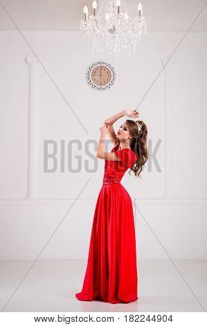 Beautiful Elegant Girl In A Long Red Dress And Shoes Is Standing In A White Room, A Portrait Of A Gi