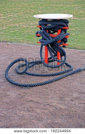 Black sports rope with an iron coil on the edge of the stadium