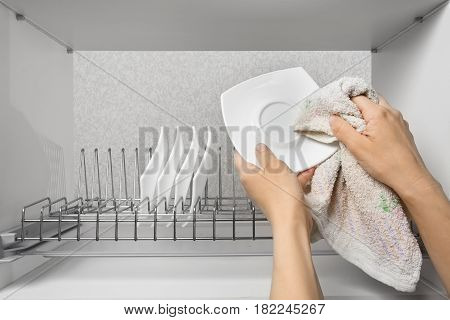 hands wiping clean plate with towel in the kitchen