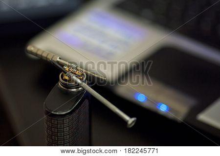 Vape after-sales service of the e-cigarette. Regulating of electronic cigarette coils. Personal vaporizer. Close up.