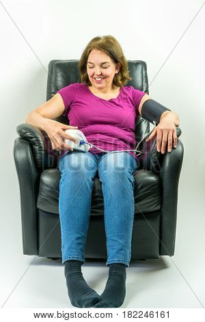 Pretty middle-age woman sitting up right in black leather recliner armchair. Checking blood pressure using portable blood pressure machine.
