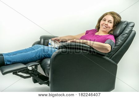 Pretty middle-age woman sitting in black leather recliner armchair. Checking blood pressure using portable blood pressure machine.
