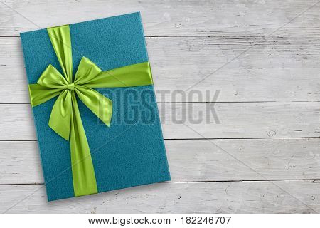 Blue gift box with green ribbon over light wood, top view from above background