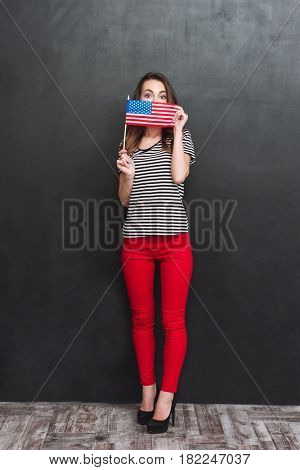 Full length portrait of a woman hiding behing a USA flag over black background