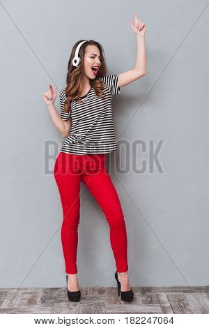 Full length portrait of a happy woman listening to music and dancing with closed eyes in studio over gray background. Vertical image