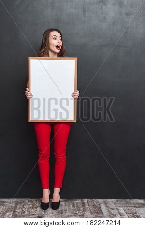 Full length portrait of a surprised woman holdink blank board and looking away. Vertical image