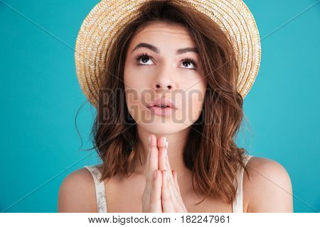 Close up portrait of a young religious girl in straw hat praying for a vacation isolated over blue background