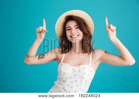 Portrait of a smiling pretty summer girl in straw hat pointing two fingers up at copyspace isolated over blue background