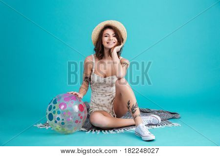 Portrait of a happy pretty summer girl sitting on a blanket and leaning on a beachball isolated over blue background