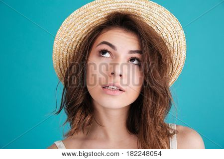 Close up portrait of a thoughtful young woman in straw hat wondering and looking away isolated over blue background
