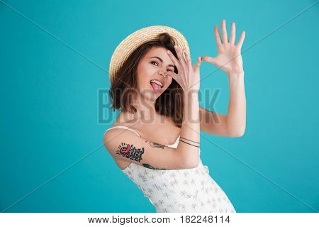 Portrait of a young silly beach girl wearing summer clothes and teasing with hands at her nose isolated over blue background