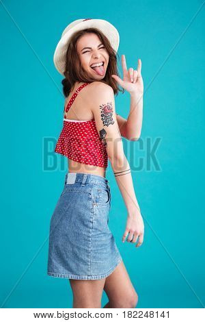 Portrait of a funny naughty girl in hat showing rock sign with fingers isolated over blue background