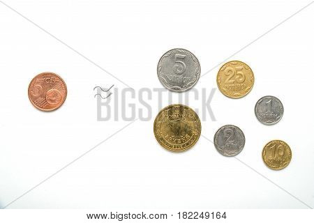 Ukrainian national coins and five euro cents against the background of the national flag. Currency of Eurovision. The exchange rate of the hryvnia to the euro