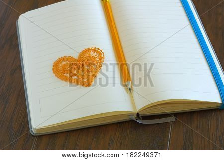 Heart symbol with pencil on open blank notebook page. Love message romance concept. Lyrics loveletter book.