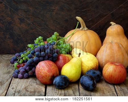Still Life Of Autumn Fruits: Pumpkin, Grape, Apple, Pear, Plum On A Wooden Background. Selective Foc