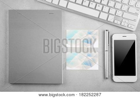 Stationery with business cards, computer and smart-phone on light table