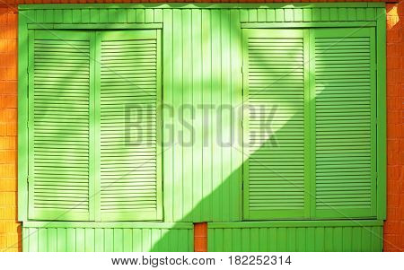 Bright green jalousie with brick wall background
