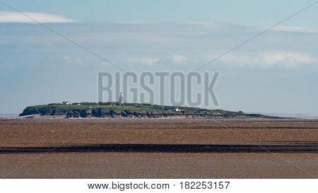 Buildings on Flat Holm Island in the Bristol Channel. Lighthouse and other buildings at low tide seen from Cardiff Bay Wales UK
