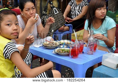 Mother With Her Daughters Eating Street Food, Sea Snails With Vegetables In Saigon