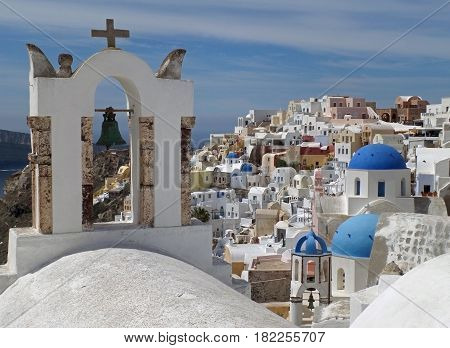 Greek Islands style white bell-tower and blue domes of the church at Oia village, Santorini island, Greece