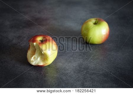Two Ripe Apples, One Bitten And One Whole On A Dark Background.