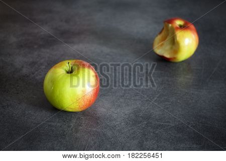 Two Ripe Apples, One Whole And One Bitten On A Dark Background.