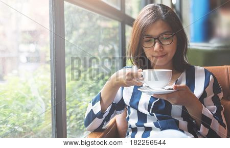 Relaxed Asian Woman holding a cup of hot coffee. Happiness eyeglasses girl smiling.