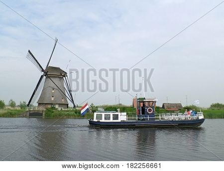 Traditional Dutch Windmill and Sightseeing Boat on the canal of Kinderdijk, Molenwaard, Netherlands