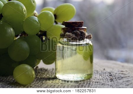 Grape seeds oil in a glass jar and fresh grapes on blurred background.Bottle of organic grape seed oil for spa and bodycare.Spa,Bio,Eco products concept.Selective focus.