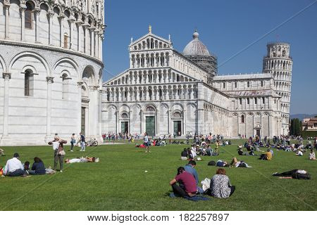 PISA, ITALY - APRIL 7, 2017: Tourists packing the cathedral of Santa Maria Assunta and leaning tower in Piazza dei Miracoli also known as Piazza del Duomo, Pisa, Italy