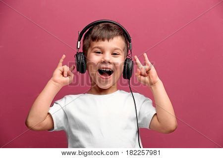 Cute little boy in headphones listening to music on color background