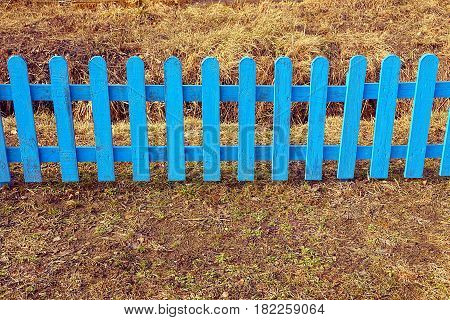 Blue wooden fences of small planks in dry grass