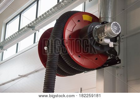 Close-up photo of the rd automobile fumes extractor in the car service station