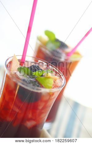 Closeup view of chilled wine cocktails with fresh apple and blackberries with mint