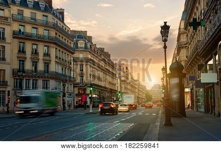 Wide street with road and beautiful architecture in Paris at sunrise, France