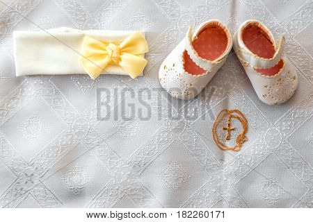 Christening details. On white baby shoes and bandage.