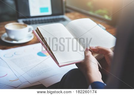 Closeup business woman hands holding notebook. Graph financial diagram documents laptop and cup of coffee on wooden table.