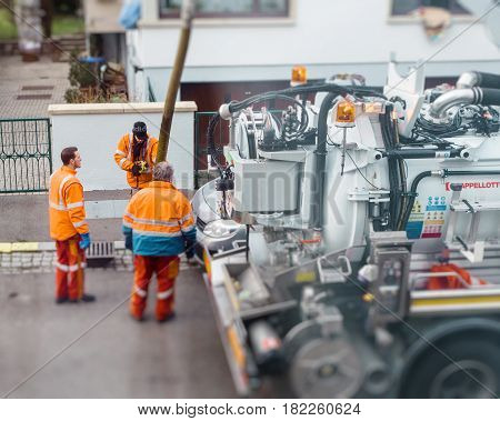 PARIS FRANCE - DEB 10 2017: Three people team working hard on the street using sewerage truck and large pipe attached to sewerage truck