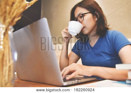 Asian eyeglasses Woman drinking hot coffee and using laptop about her job.