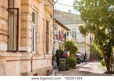 Bucharest old street with woman silhouette walking - typical old Bucharest architecture with vintagebuilding on a sunny day