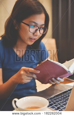 Close up Woman reading a book. Happiness Asian girl with laptop and a cup of tea at her workplace.