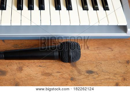Electronic synthesizer keyboard with many control knobs in silver plastic body and black voice microphone on wooden background front view closeup