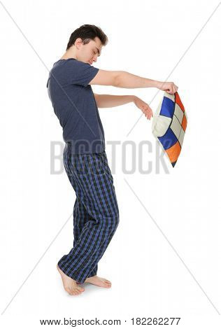 Young sleepy man with pillow suffering from somnambulism on white background