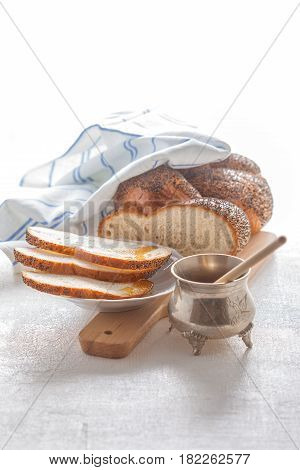 Braided Challah bread and honey on the table