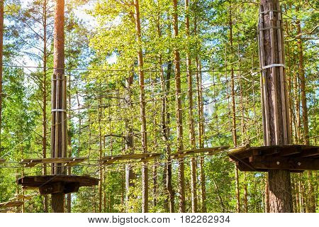 Hinged trail in extreme rope Park in summer forest. High-altitude climbing training on adventure track equipped with safety straps. Estonian summer