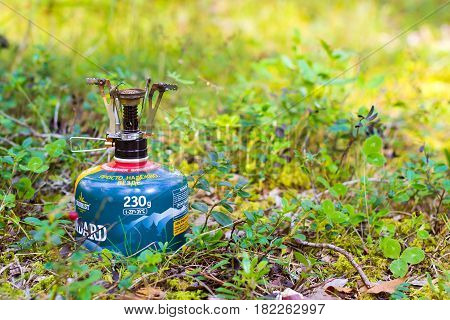 Alutaguse Seikluspark Estonia - August 28 2016: Touristic camping burner installed on gas cylinder tank in background of forest. Compact kitchen stove for cooking hot food in field travel conditions