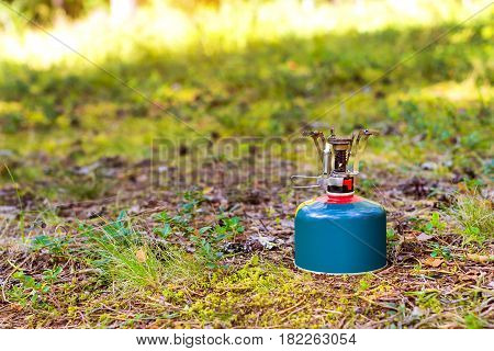 Touristic camping burner installed on gas cylinder tank in background of summer forest. Compact kitchen stove for cooking hot food in field travel conditions