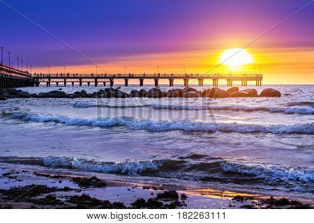 Pedestrian pier extends into the sea. Sunset at Baltic sea in resort Palanga Lithuania. Rays of sun shine through the low cirrus clouds. Tidal waves wash the sandy beach in cloudy weather
